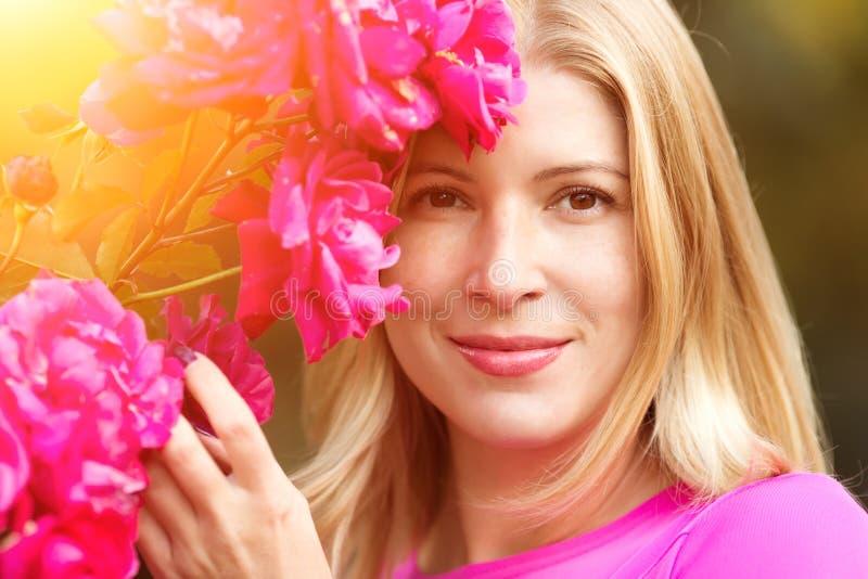 Mujer joven de la moda de la primavera con las rosas en jardín de la primavera springti foto de archivo libre de regalías