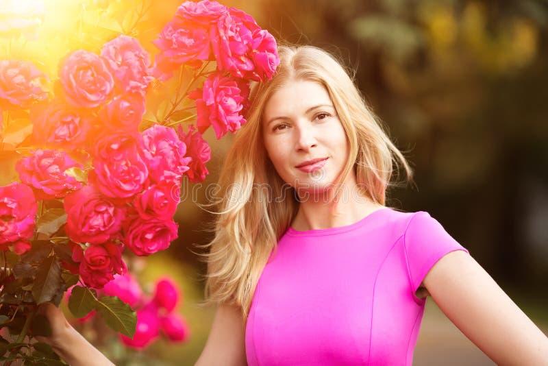 Mujer joven de la moda de la primavera con las rosas en jardín de la primavera springti imagen de archivo libre de regalías