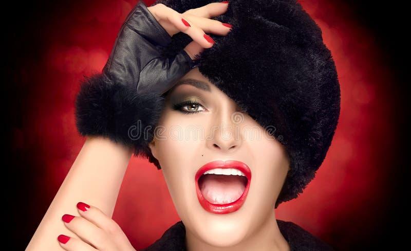 Mujer joven de la moda del invierno en sombrero de piel que gesticula y que hace muecas fotos de archivo