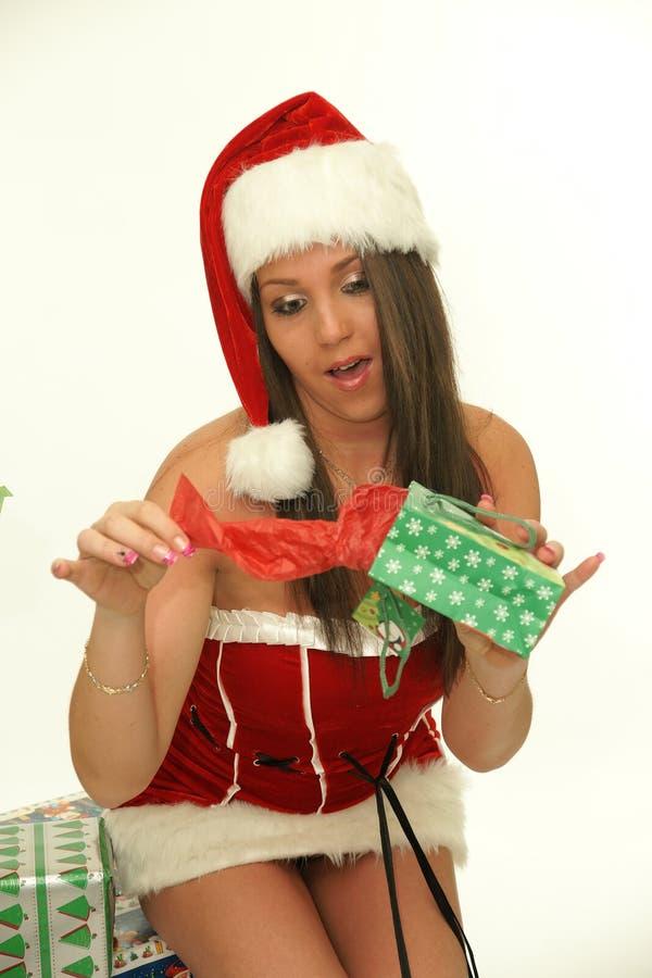 Mujer joven de la Navidad que abre el regalo imagen de archivo libre de regalías