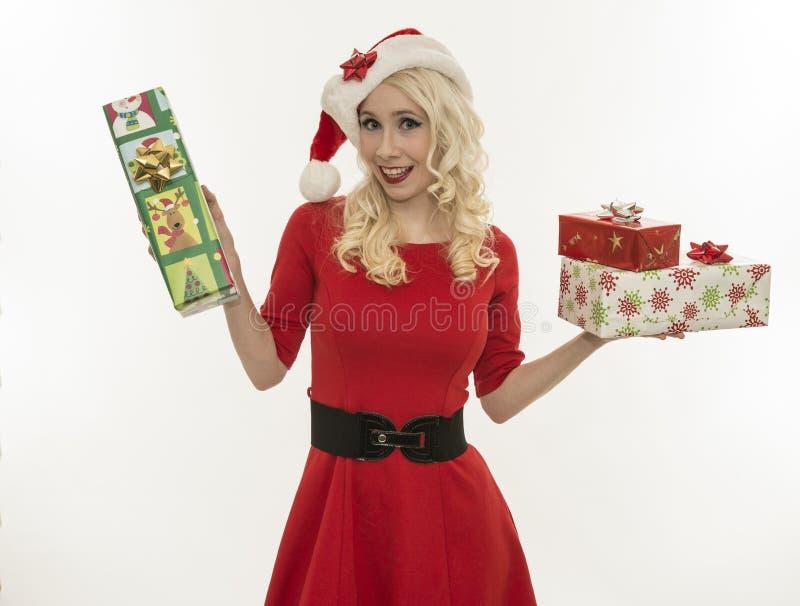 Mujer joven de la Navidad que sostiene los regalos imagen de archivo
