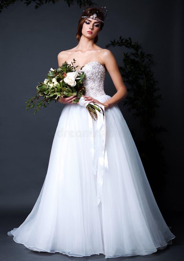 Mujer joven de la novia en vestido de boda en fondo gris imagen de archivo libre de regalías