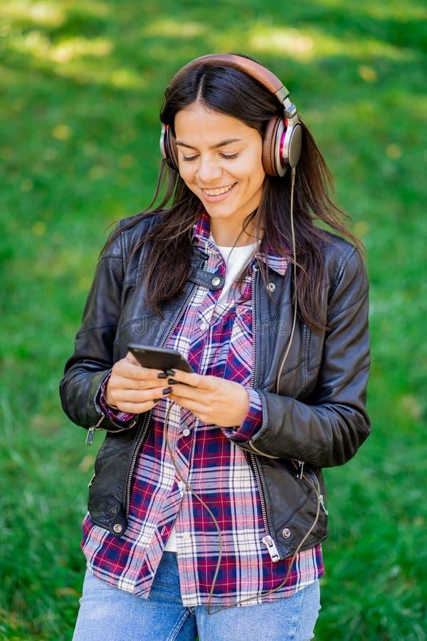 Mujer joven de la raza mixta hermosa que escucha la música en los auriculares con smartphone Baile hispánico de la muchacha del i imágenes de archivo libres de regalías
