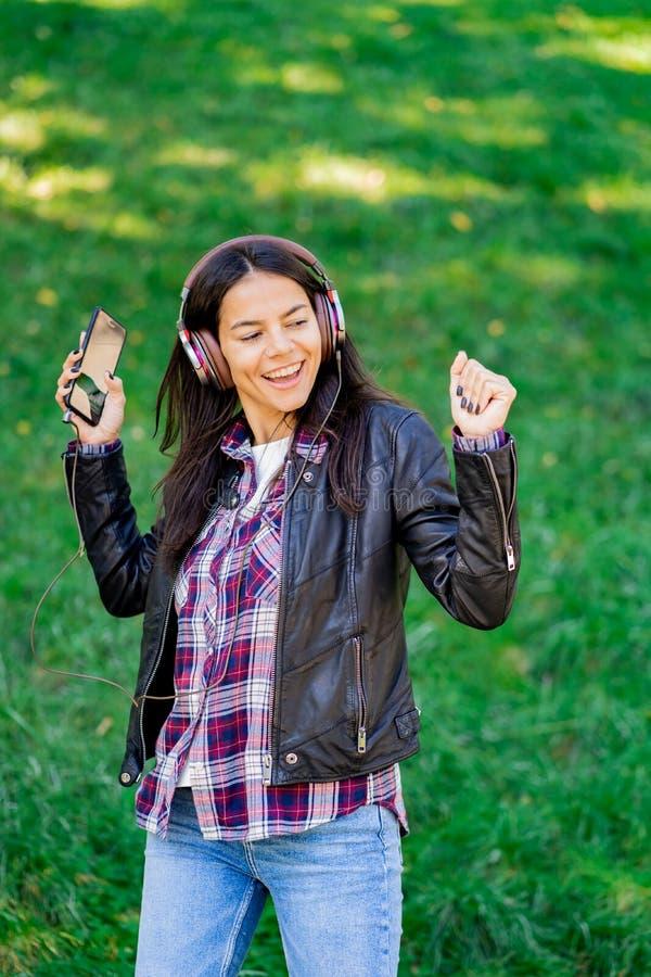 Mujer joven de la raza mixta hermosa que escucha la música en los auriculares con smartphone Baile hispánico de la muchacha del i fotos de archivo