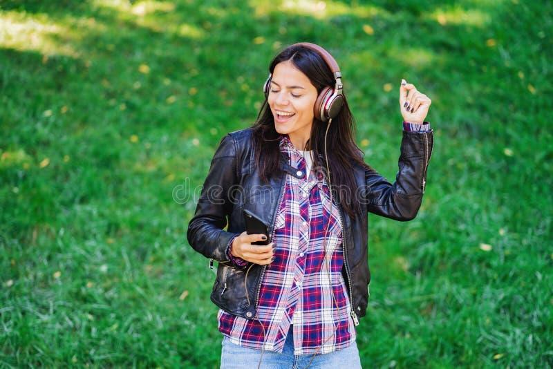Mujer joven de la raza mixta hermosa que escucha la música en los auriculares con smartphone Baile hispánico de la muchacha del i imagen de archivo libre de regalías