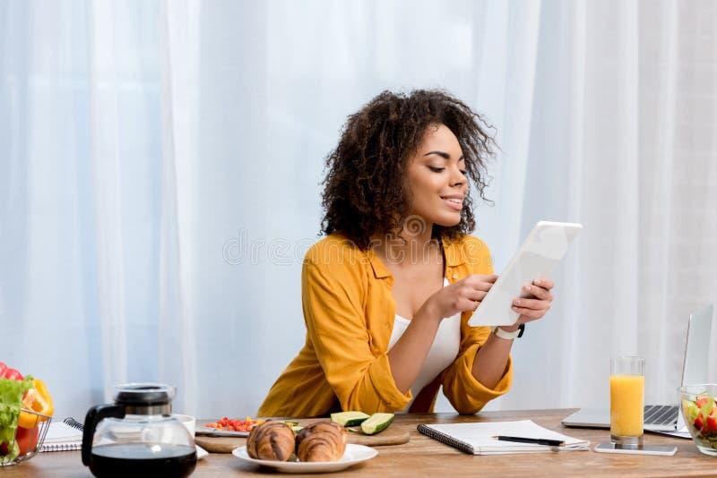 mujer joven de la raza mixta que usa la tableta en la cocina con la comida imágenes de archivo libres de regalías