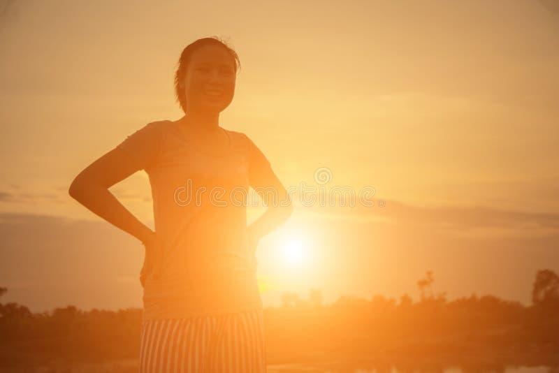 Mujer joven de la silueta en la puesta del sol imagen de archivo libre de regalías