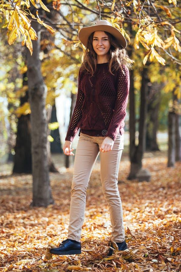 Mujer joven de la sonrisa feliz que camina al aire libre en parque del otoño en suéter y sombrero acogedores Tiempo soleado calie fotos de archivo