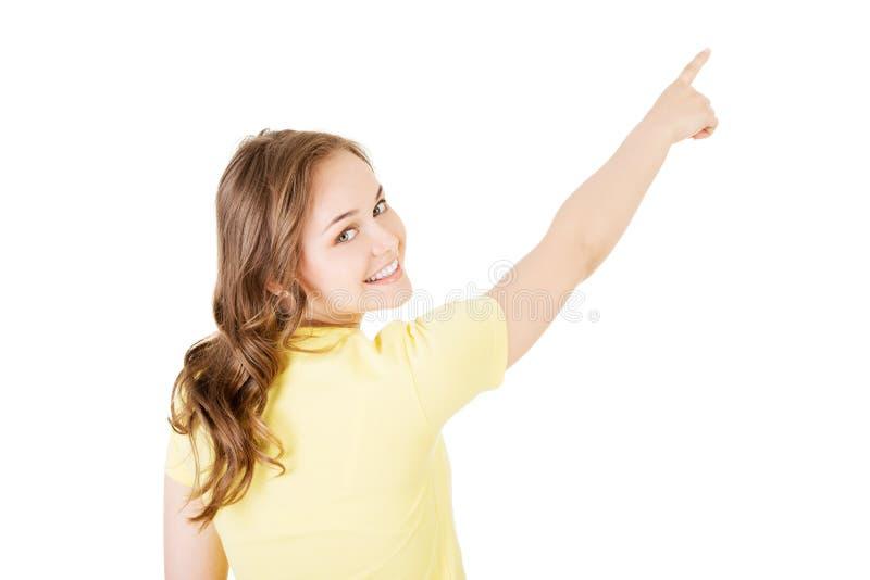 Mujer joven de la visión trasera que señala hasta la esquina fotos de archivo libres de regalías