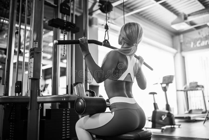 Mujer joven de los deportes hermosos que presenta en gimnasio de la aptitud imagen de archivo