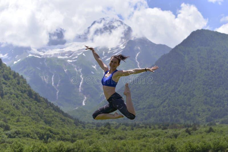 Mujer joven de los deportes que hace yoga en la hierba verde en el verano fotografía de archivo libre de regalías