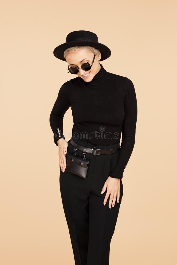 Mujer joven de moda del inconformista con el pelo corto rubio que lleva la presentación elegante negra de la ropa, del sombrero y imagenes de archivo