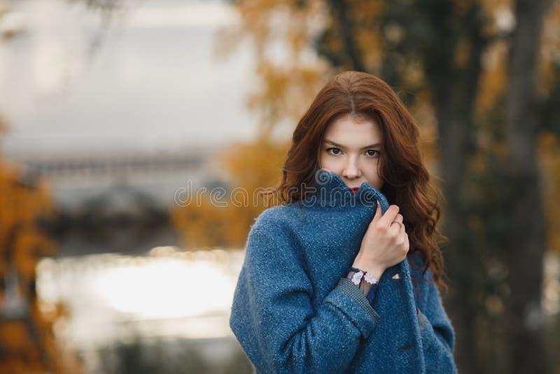 Mujer joven de moda en la capa azul caliente que presenta en el parque del otoño Ella que cierra la capa por sus manos imagen de archivo