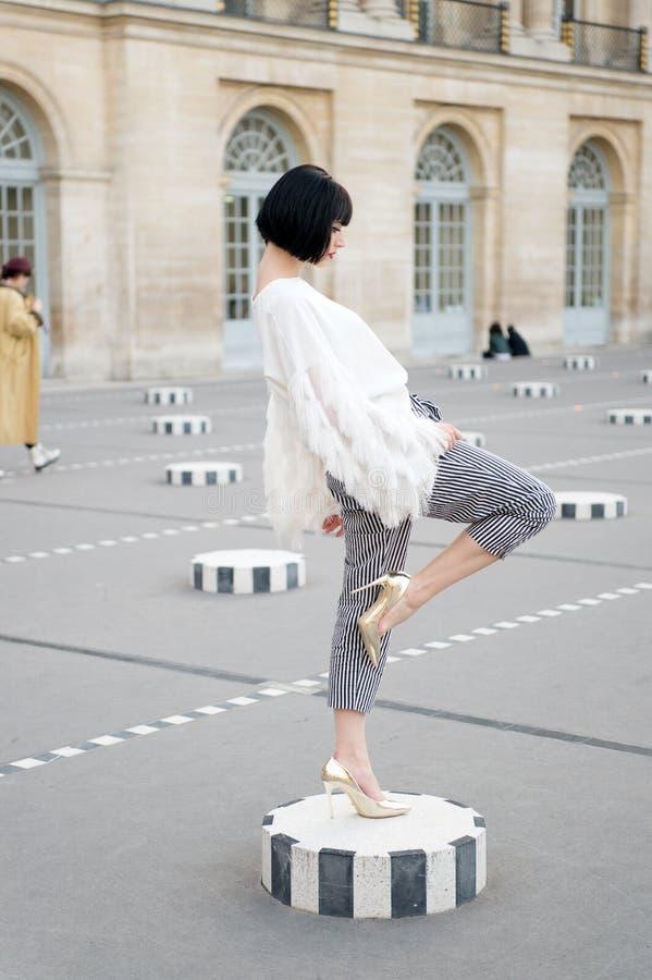 Mujer joven de moda en los zapatos blancos de la blusa y del tacón alto en las calles de la ciudad Moda en París, Francia foto de archivo libre de regalías