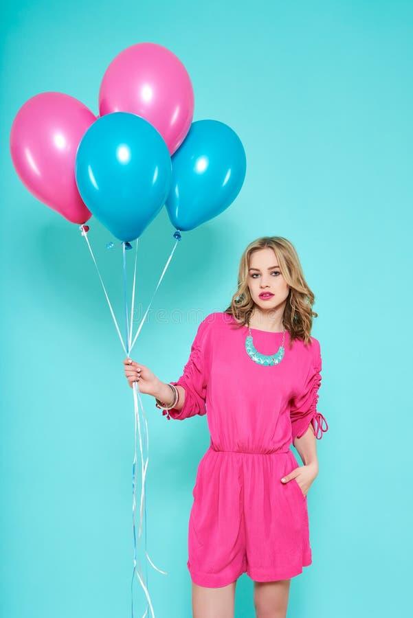Mujer joven de moda magnífica en el equipo del partido que sostiene el manojo de globos Concepto de la fiesta de cumpleaños foto de archivo