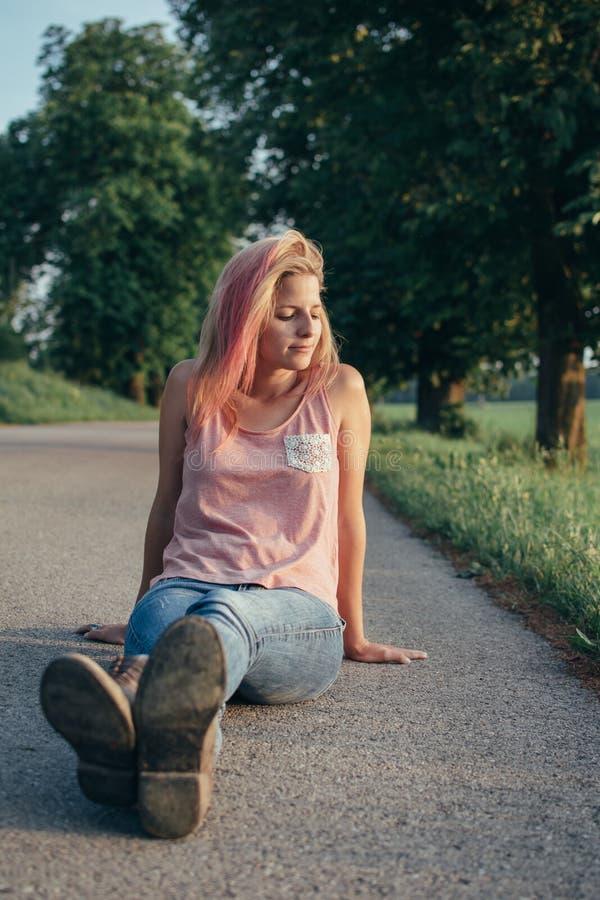 Mujer joven de moda que se sienta en el camino imagenes de archivo