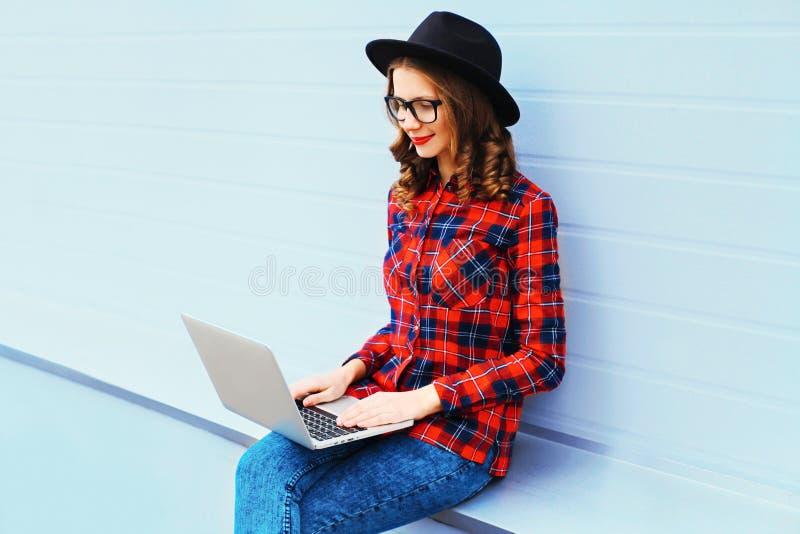 Mujer joven de moda que trabaja usando el ordenador portátil al aire libre imagen de archivo