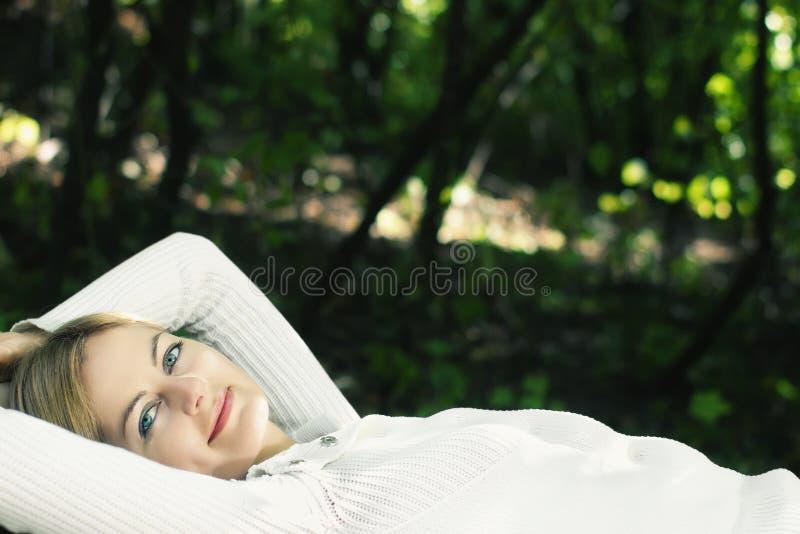 Mujer joven de ojos azules de mentira en el bosque foto de archivo libre de regalías
