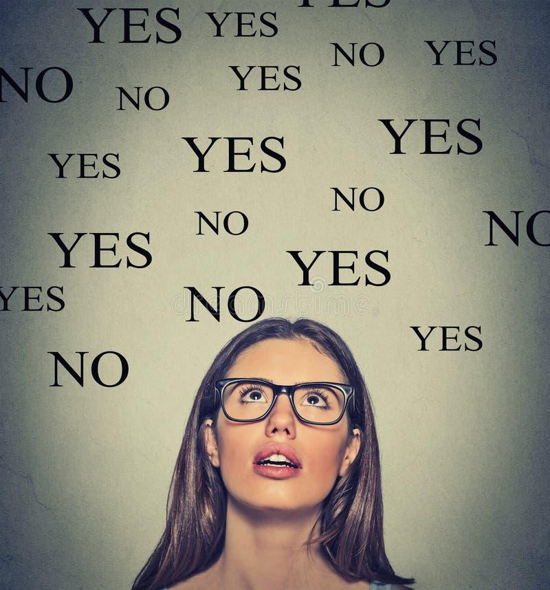 Mujer joven de pensamiento con el sí o ninguna opción que mira para arriba fotografía de archivo libre de regalías