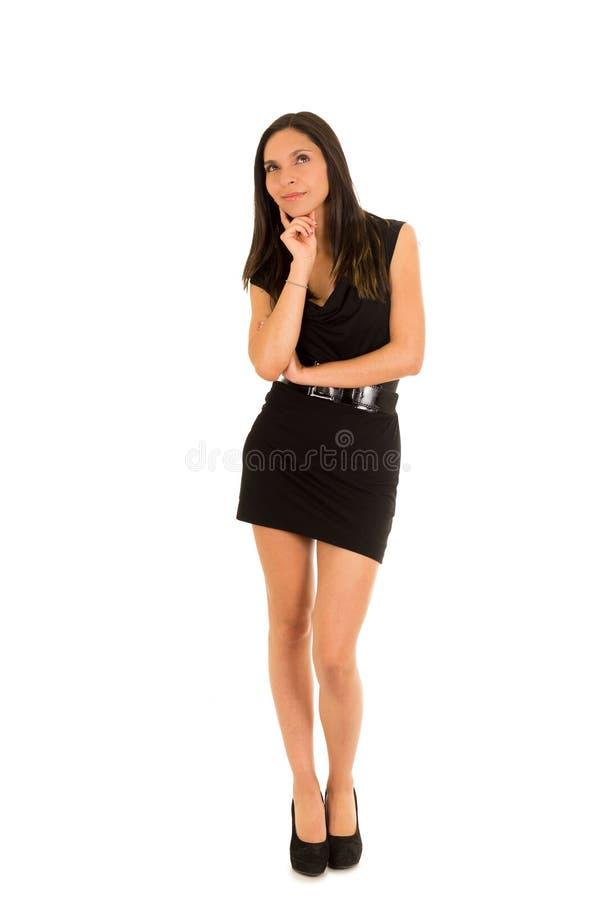 Mujer joven de pensamiento hermosa, llevando un vestido negro y presentando para la cámara, en un fondo blanco foto de archivo libre de regalías