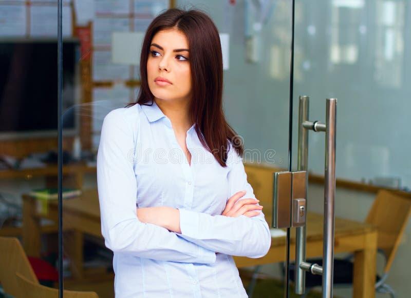 Mujer joven de pensamiento que mira lejos en oficina imagen de archivo libre de regalías