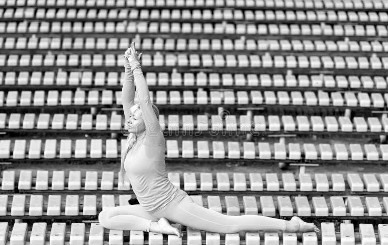 Mujer joven de Preatty que hace asanas de la yoga en el parque fotos de archivo