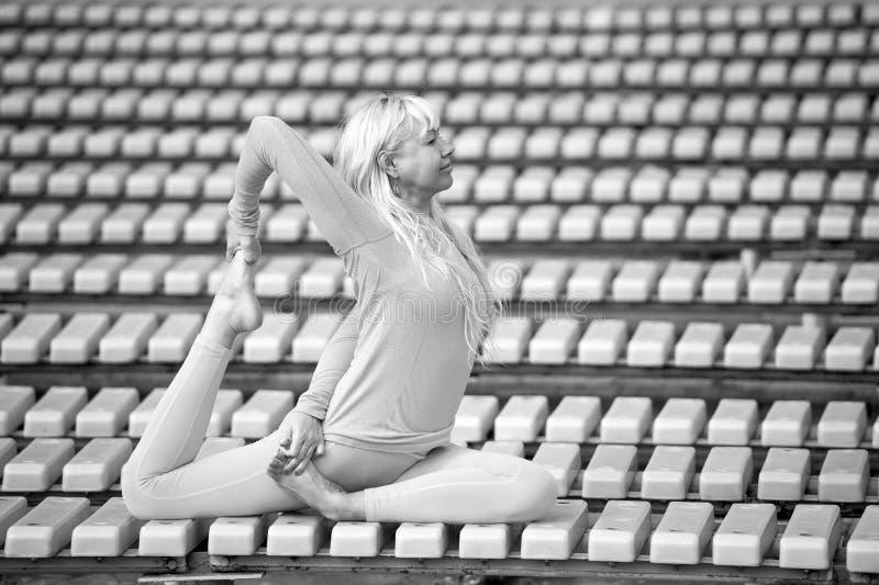 Mujer joven de Preatty que hace asanas de la yoga en el parque imagen de archivo