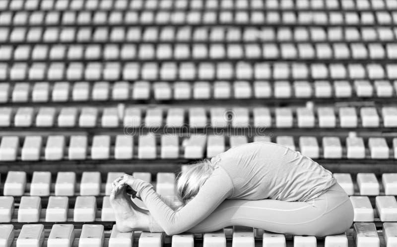 Mujer joven de Preatty que hace asanas de la yoga en el parque imagenes de archivo