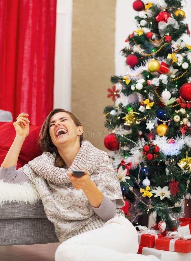 Mujer joven de risa con el árbol de navidad cercano teledirigido de la TV imagen de archivo