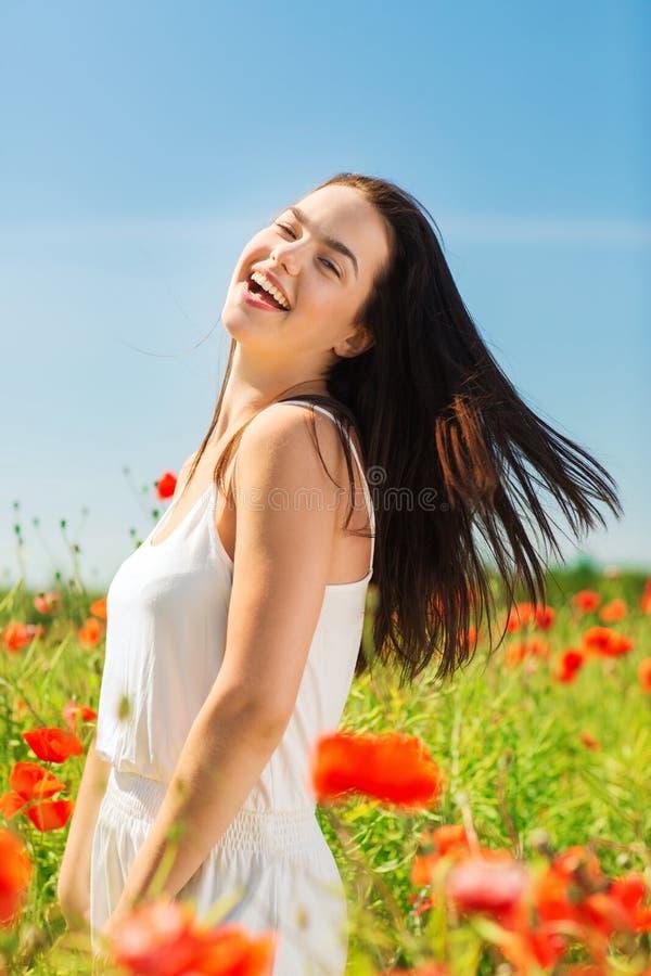 Mujer joven de risa en campo de la amapola fotografía de archivo