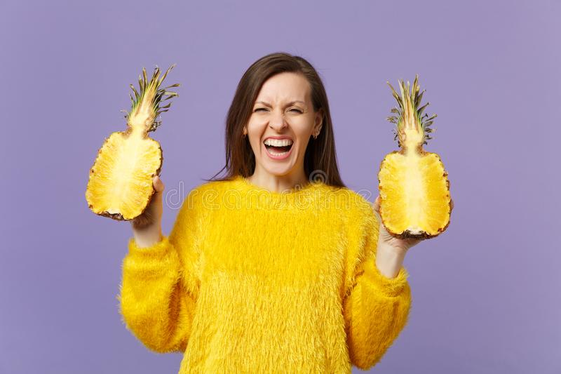 Mujer joven de risa en el suéter de la piel que se sostiene en halfs de las manos de la fruta madura fresca de la piña aislada en foto de archivo
