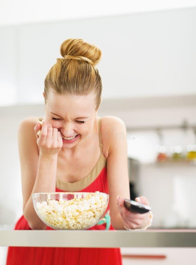 Mujer joven de risa que come las palomitas y que ve la TV en cocina foto de archivo