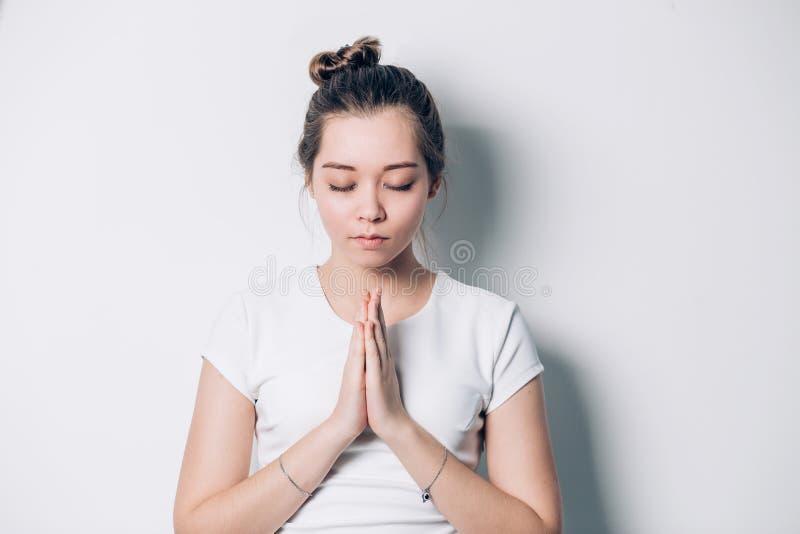Mujer joven de rogación Hembra con las manos dobladas en el blanco que mira para arriba con una petición fotos de archivo