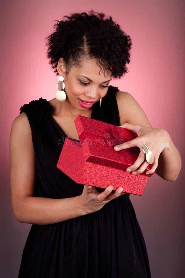 Mujer joven del afroamericano que abre un regalo foto de archivo