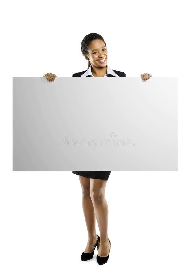 Mujer joven del afroamericano que lleva a cabo la muestra en blanco fotografía de archivo libre de regalías