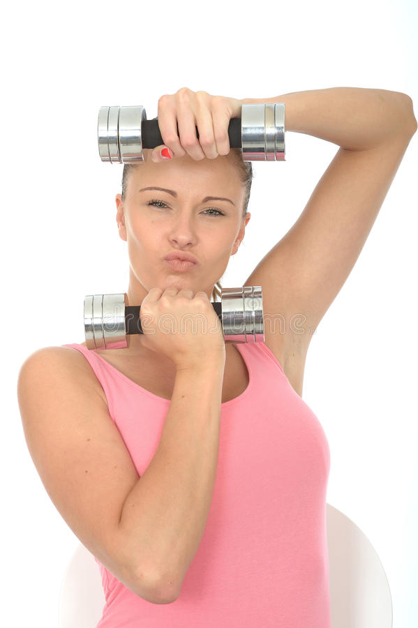 Mujer joven del ajuste resuelto sano que lleva a cabo los pesos mudos de Bell que tiran de la expresión fotos de archivo