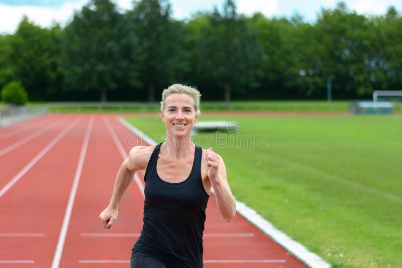 Mujer joven del ajuste sano que corre en una pista imágenes de archivo libres de regalías