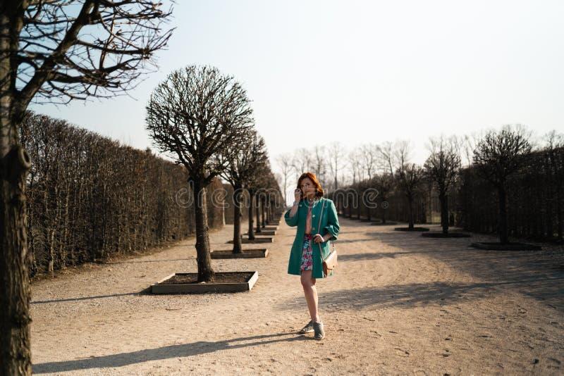 Mujer joven del amante de la moda waling en un parque que lleva la chaqueta verde viva y una falda colorida foto de archivo libre de regalías