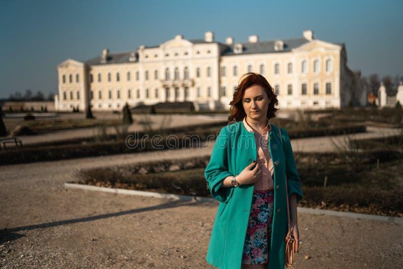 Mujer joven del amante de la moda waling en un parque que lleva la chaqueta verde viva y una falda colorida fotografía de archivo libre de regalías