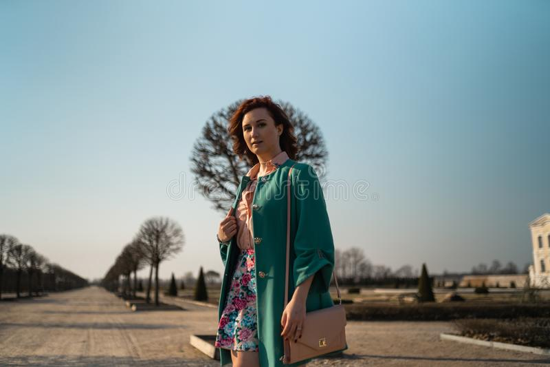 Mujer joven del amante de la moda waling en un parque que lleva la chaqueta verde viva y una falda colorida imagen de archivo libre de regalías