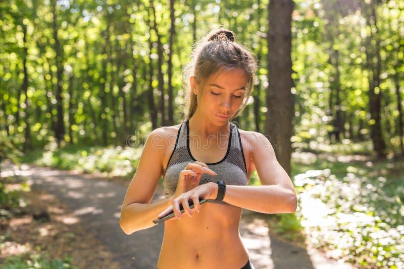 Mujer joven del atleta que comprueba progreso de la aptitud en cuanto a su reloj elegante Corredor femenino que usa la aptitud ap imagenes de archivo