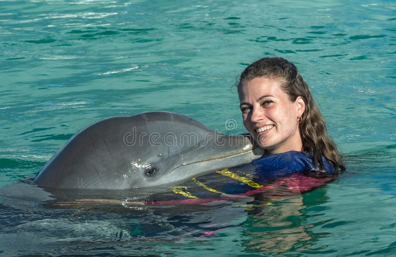 Mujer joven del beso del delf?n en agua azul Mujer sonriente que nada con el delf?n Fondo abstracto azul del agua imagen de archivo