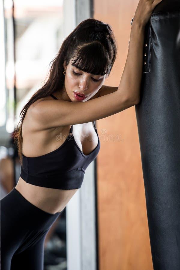 Mujer joven del boxeador hermoso cansada tomando una rotura del ejercicio que se inclina contra el saco de arena en gimnasio de l fotos de archivo