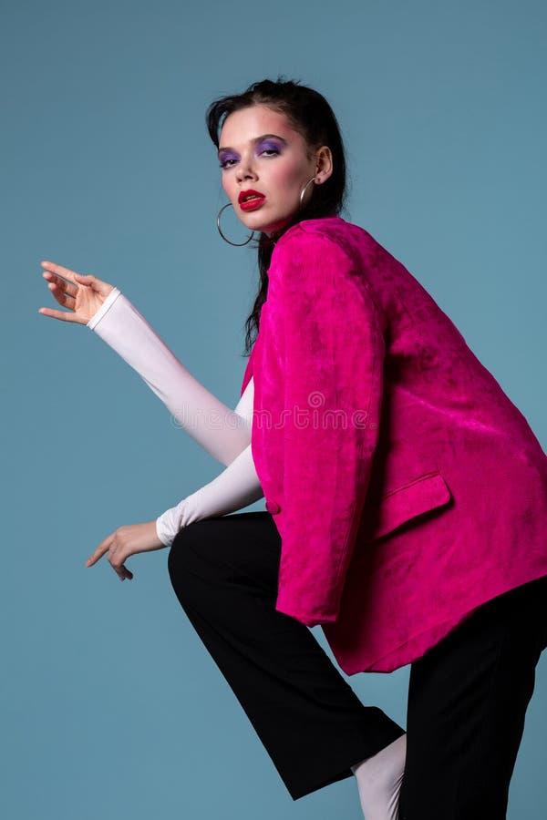 Mujer joven del brunett que sorprende en la chaqueta rosada de moda que se coloca en una pierna foto de archivo