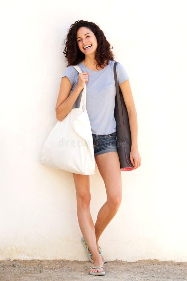 Mujer joven del cuerpo completo que sonríe con la estera y el bolso de la yoga contra el fondo blanco imágenes de archivo libres de regalías