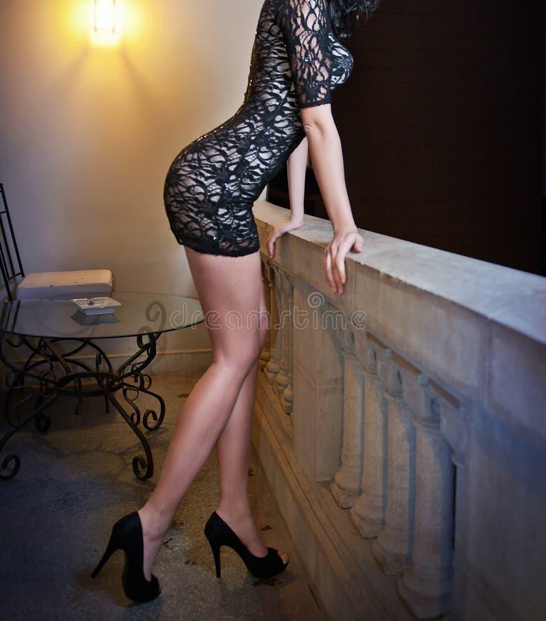 Mujer joven del cuerpo perfecto de moda en poco vestido negro que presenta en una repisa Vista lateral de la hembra sensual fotos de archivo