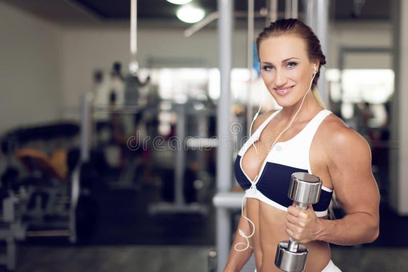 Mujer joven del culturista que lleva a cabo pesa de gimnasia en gimnasio foto de archivo libre de regalías