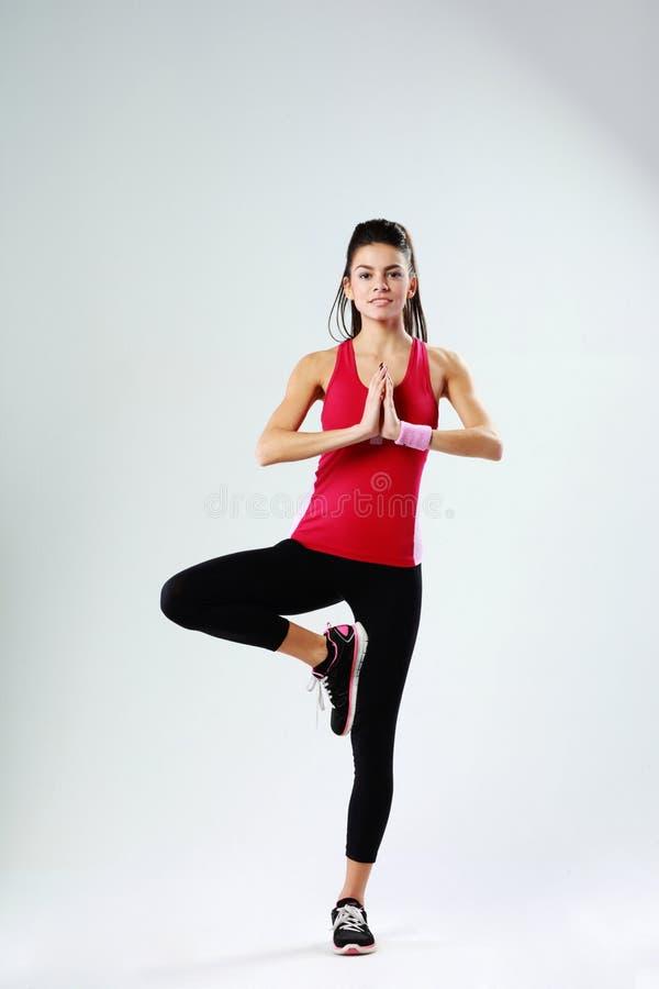 Mujer joven del deporte que medita mientras que se coloca en una pierna fotos de archivo libres de regalías