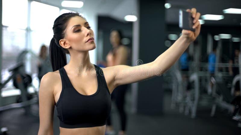Mujer joven del deporte que toma el selfie después del entrenamiento del gimnasio, plataforma social de los medios foto de archivo libre de regalías