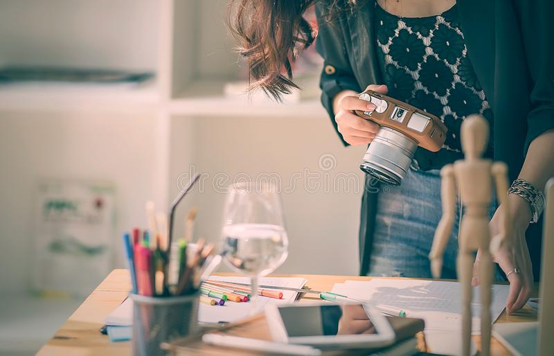 Mujer joven del diseñador que trabaja con papeleo y que sostiene la cámara fotos de archivo libres de regalías